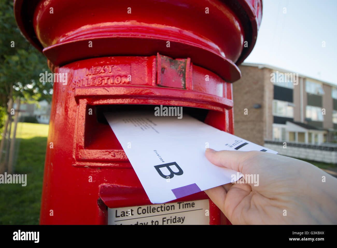 A UK postal vote being put into a post box. - Stock Image