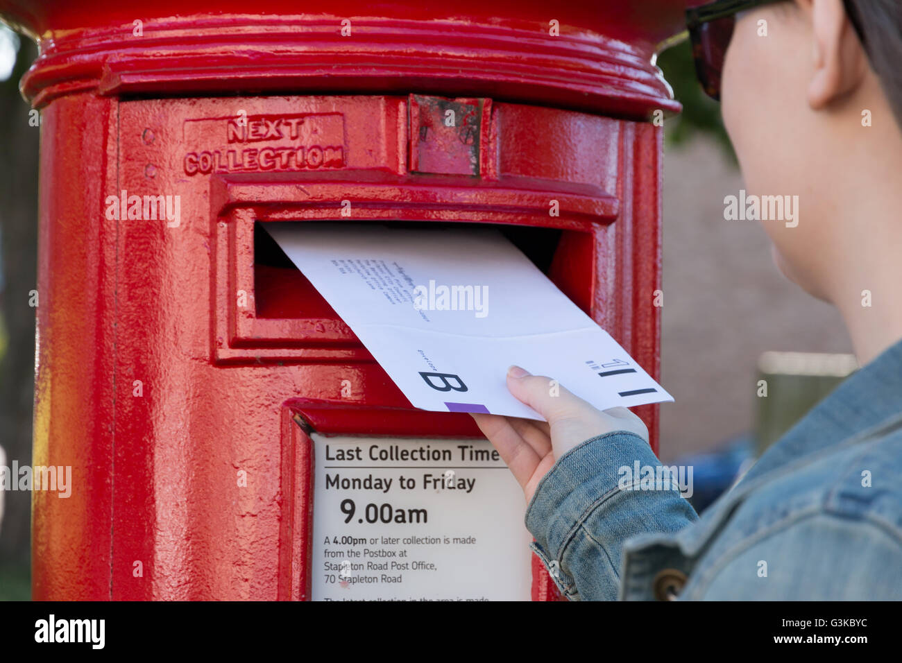 A young lady posting a postal ballot in the UK. - Stock Image