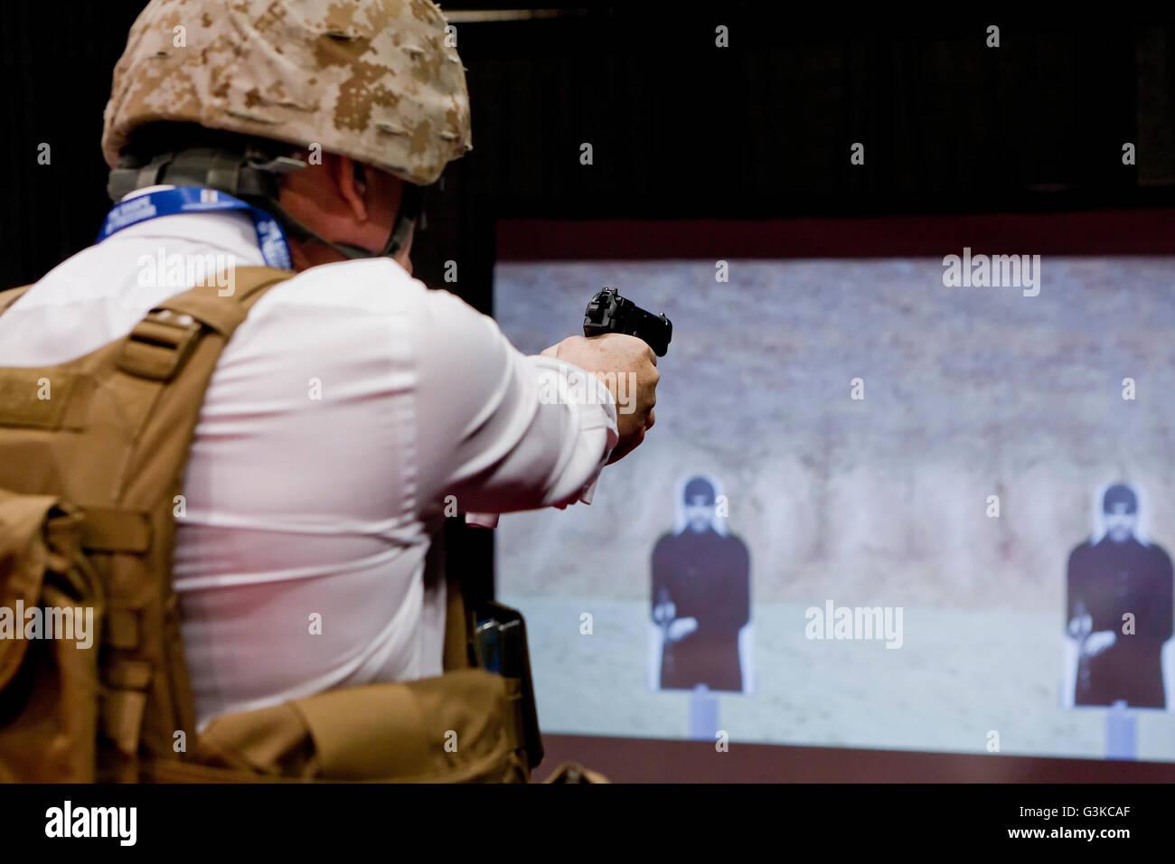Man at a target shooting simulator using a handgun - USA - Stock Image