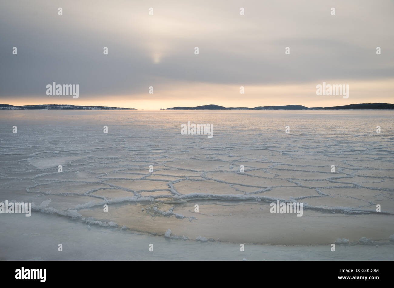 Sun low on the horizon over sea ice in the archipelago outside of Örnsköldsvik in the Northern part of - Stock Image