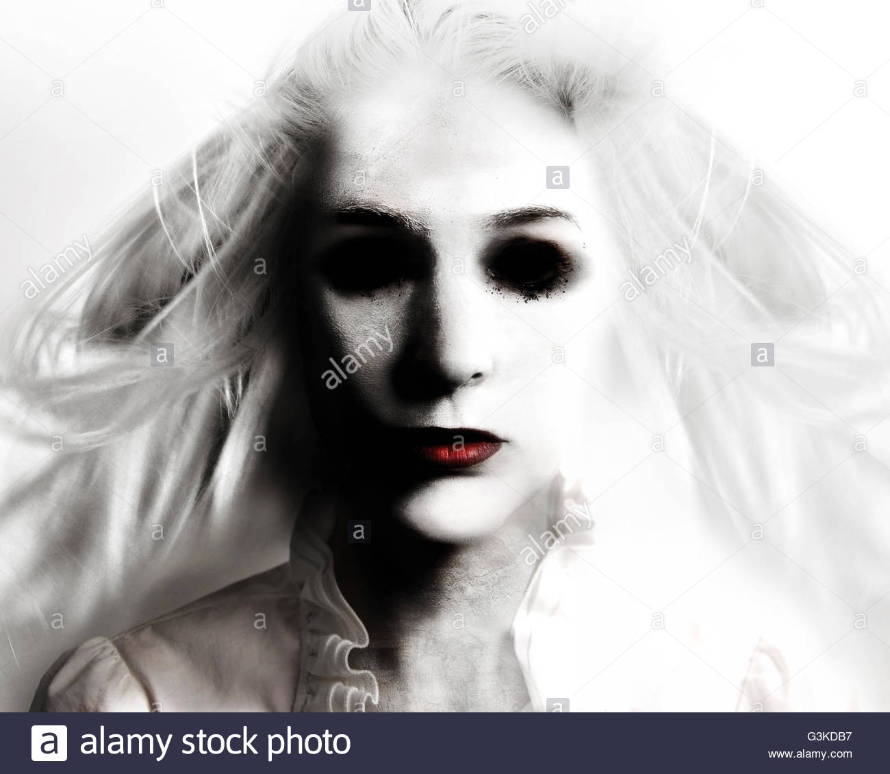 A scary evil woman with black eyes and red lips is death on a white background for a fear or Halloween concept. - Stock Image