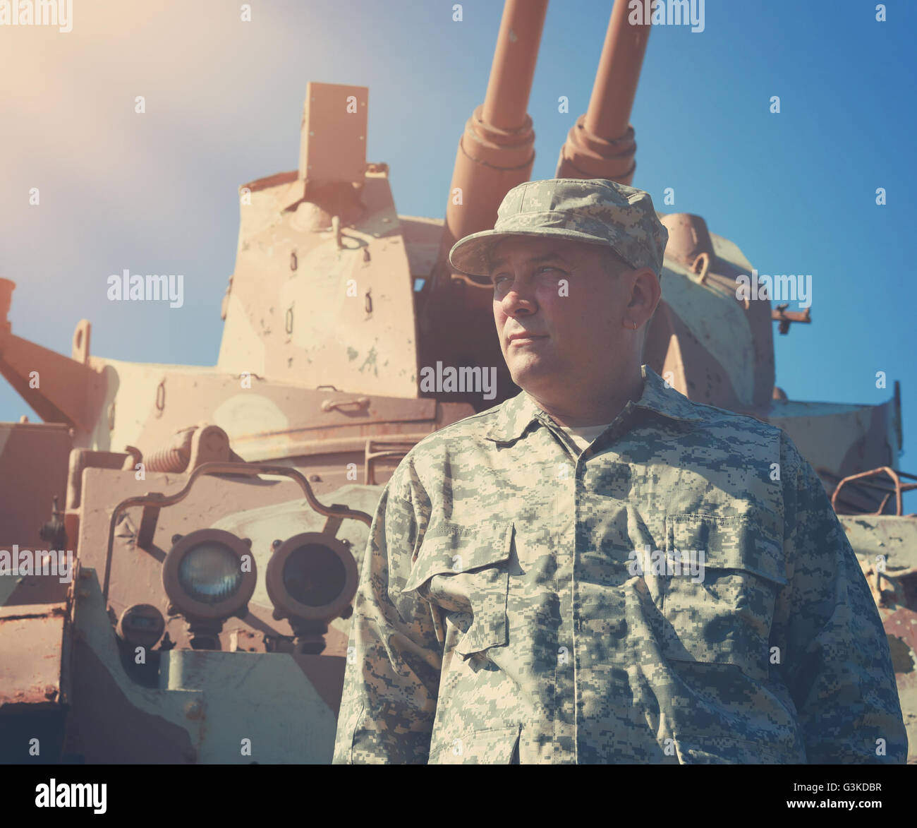 A military soldier is standing in front of an army tank vehicle with sun outside for an american war, defense or - Stock Image