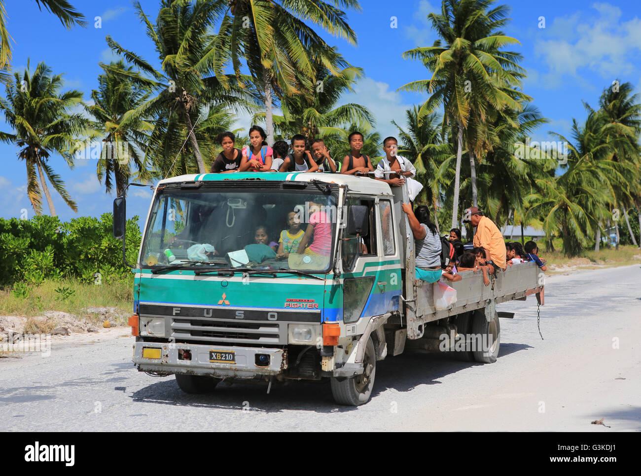 Local children hitching a ride home from school, Christmas Island, Kiribati - Stock Image