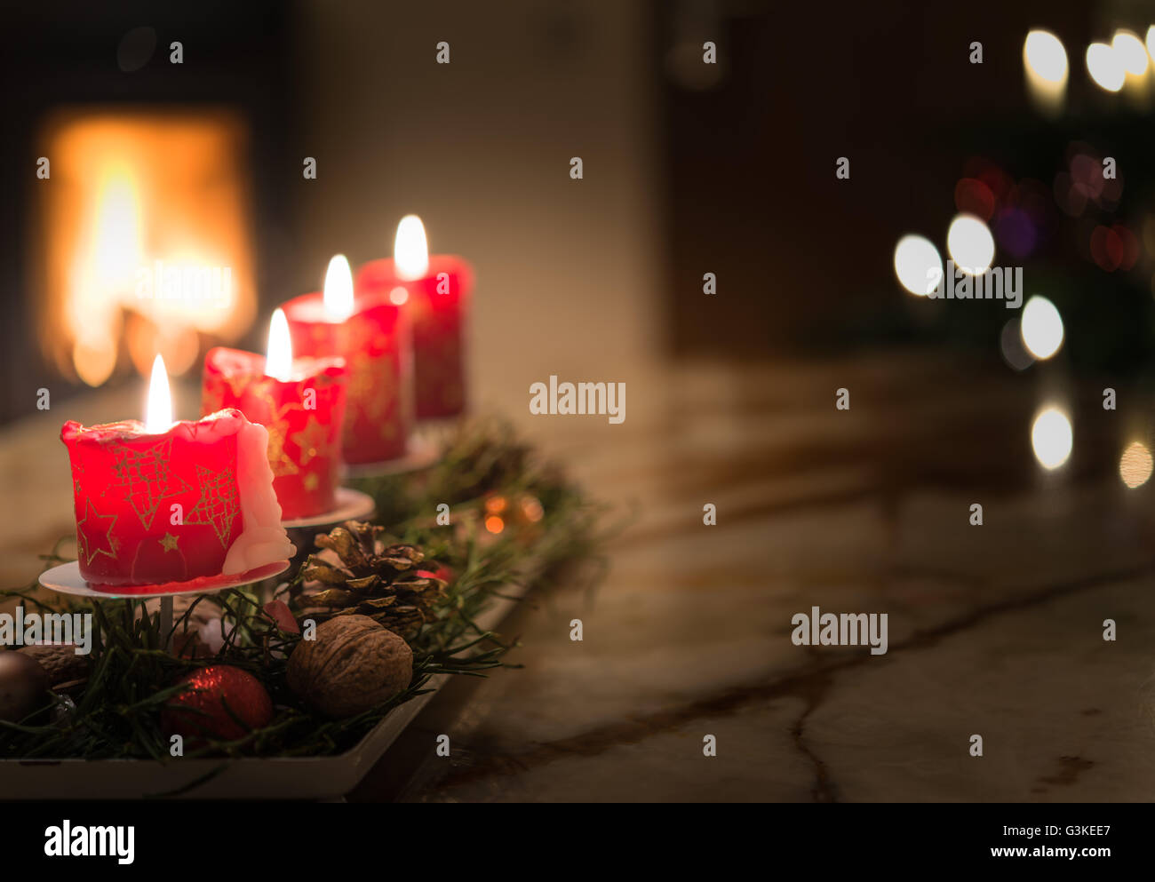 Advent candles with Christmas tree and burning chimney fire - Stock Image