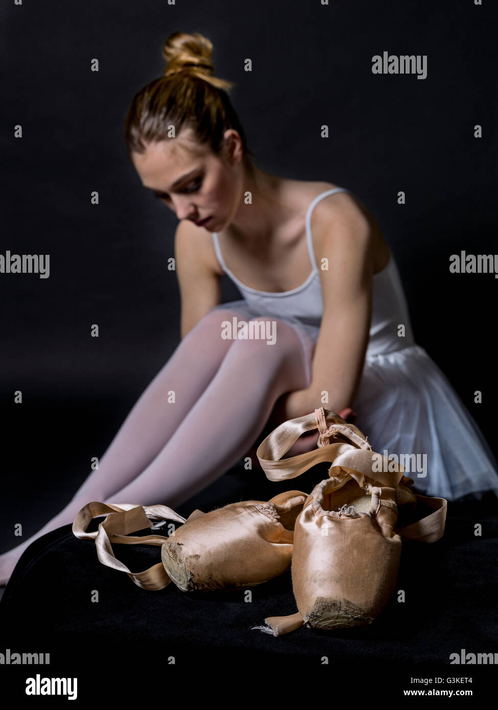 Close-up of a ballet pointe shoes, and in the background a dancer sitting, resting on black background - Stock Image