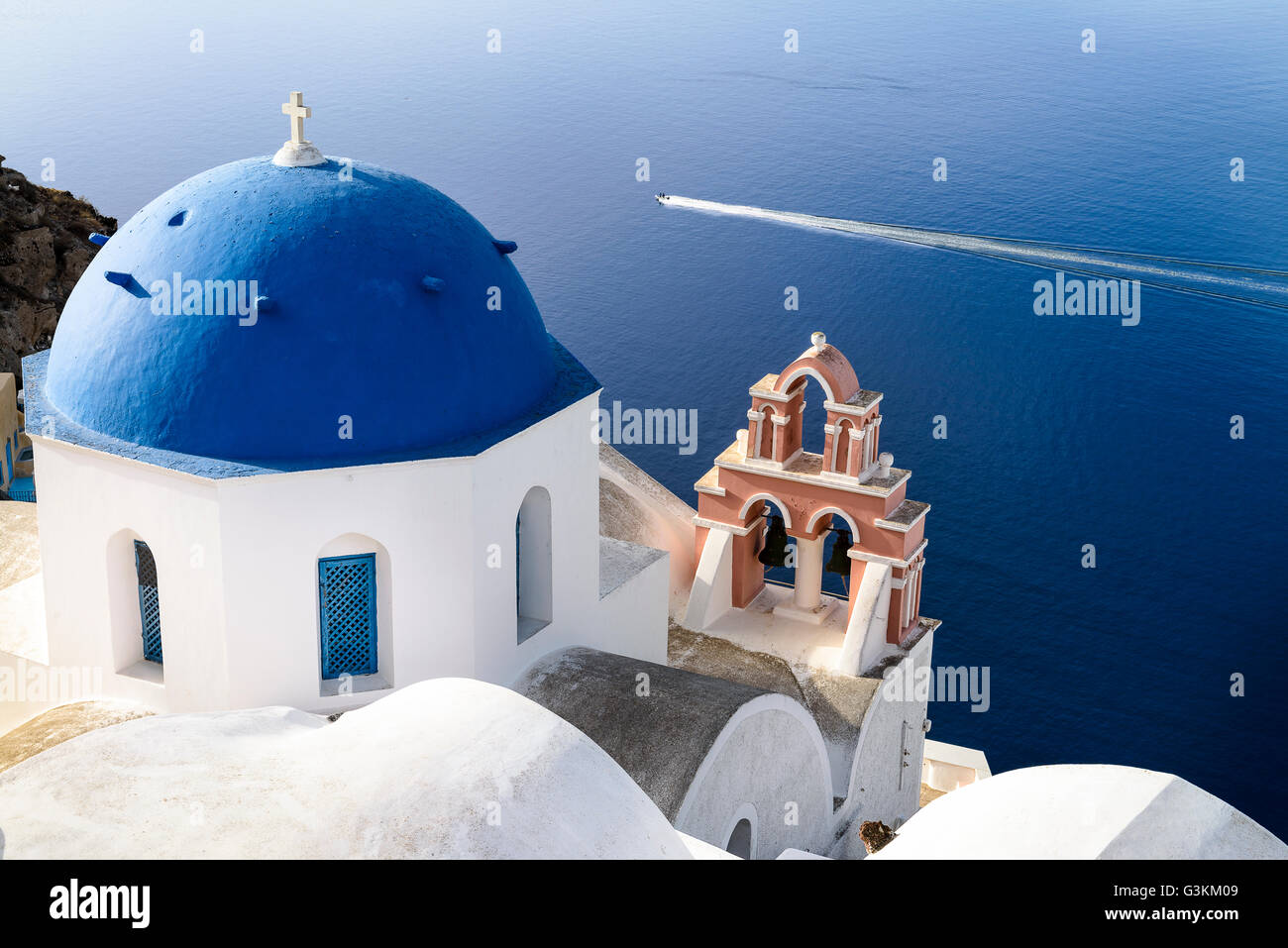Oia town on Santorini island, Greece. Traditional and famous houses and churches with blue domes over the Caldera, - Stock Image
