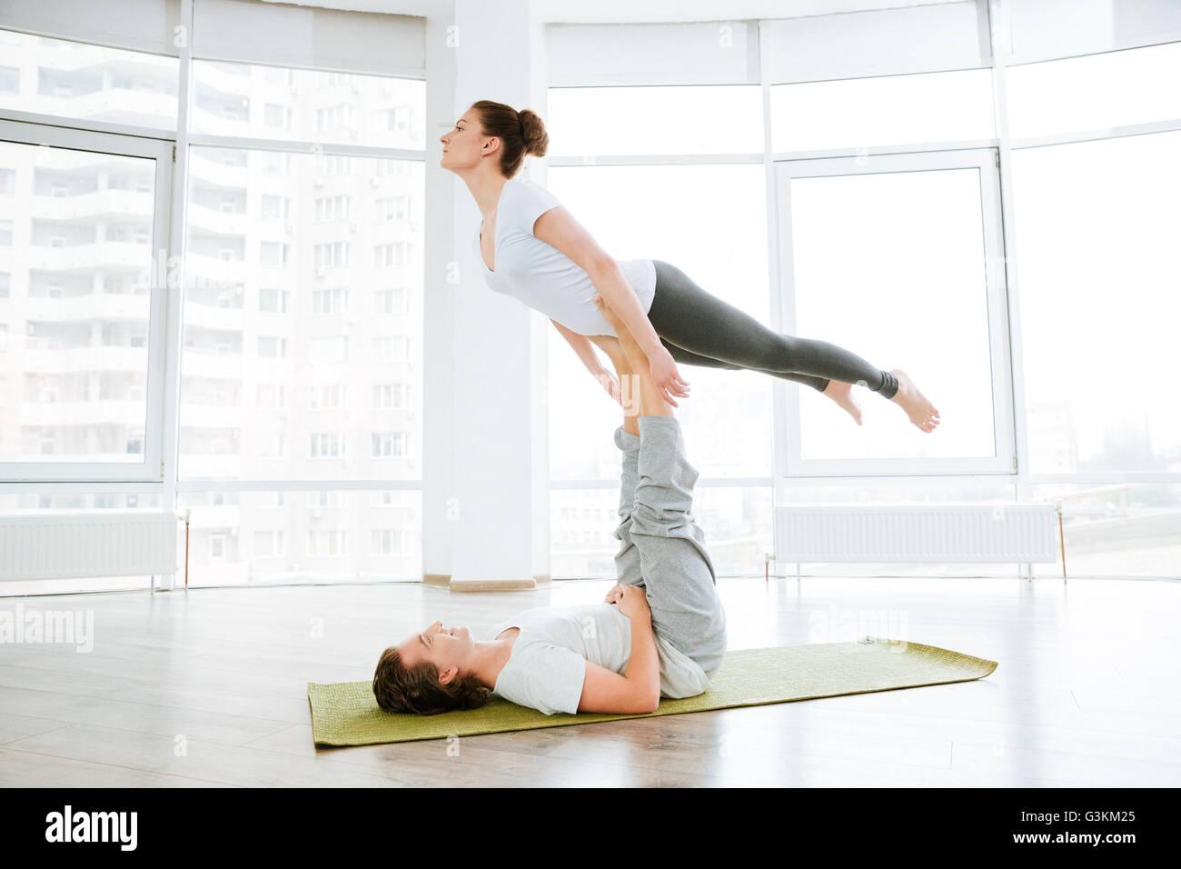 Beautiful young couple doing acro yoga in studio together Stock Photo