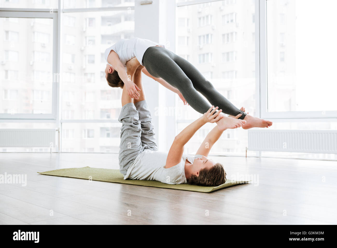 Young couple doing relaxation exercises in studio together - Stock Image