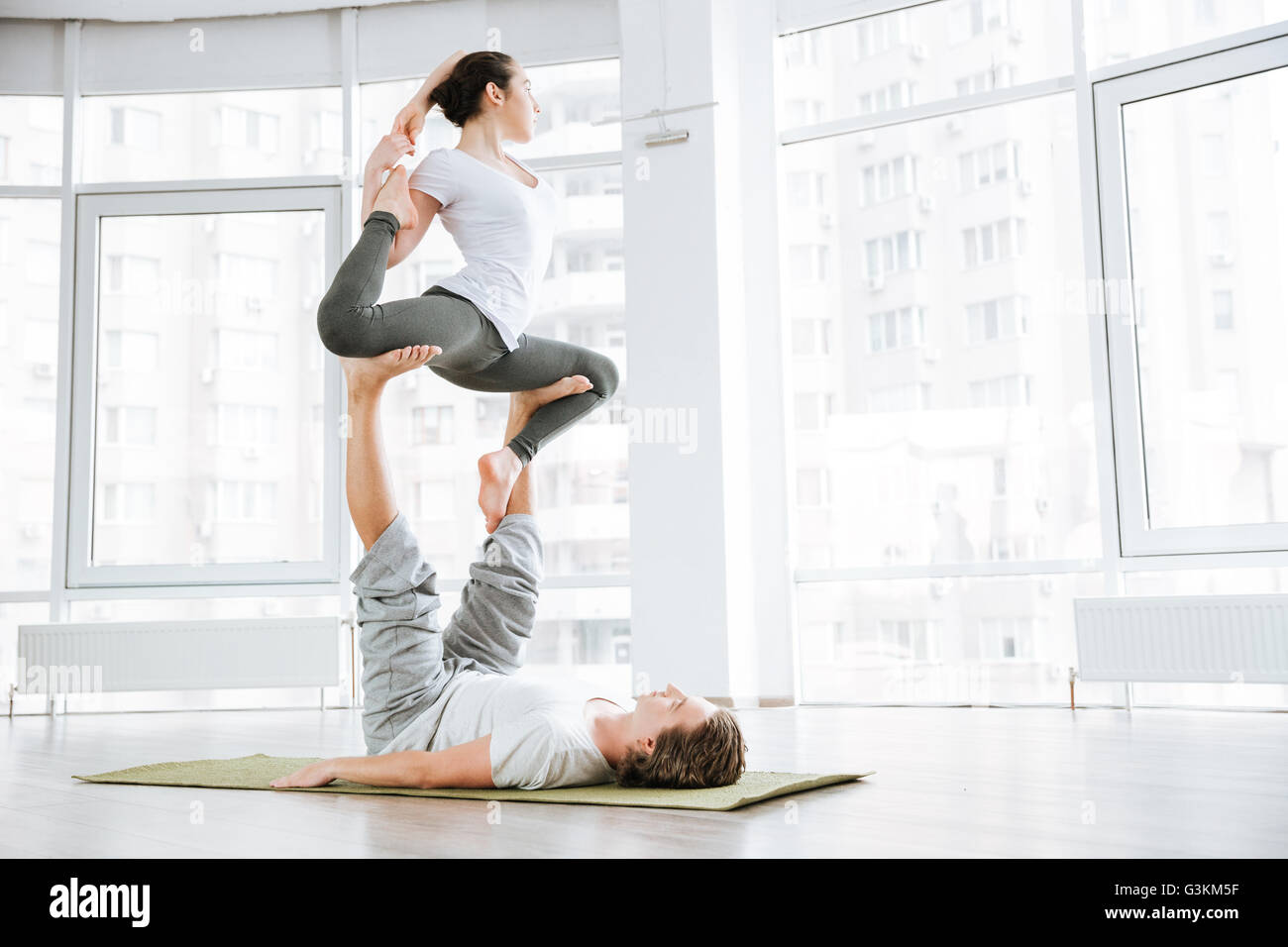 Concentrated young man and woman doing acro yoga for couples in studio - Stock Image