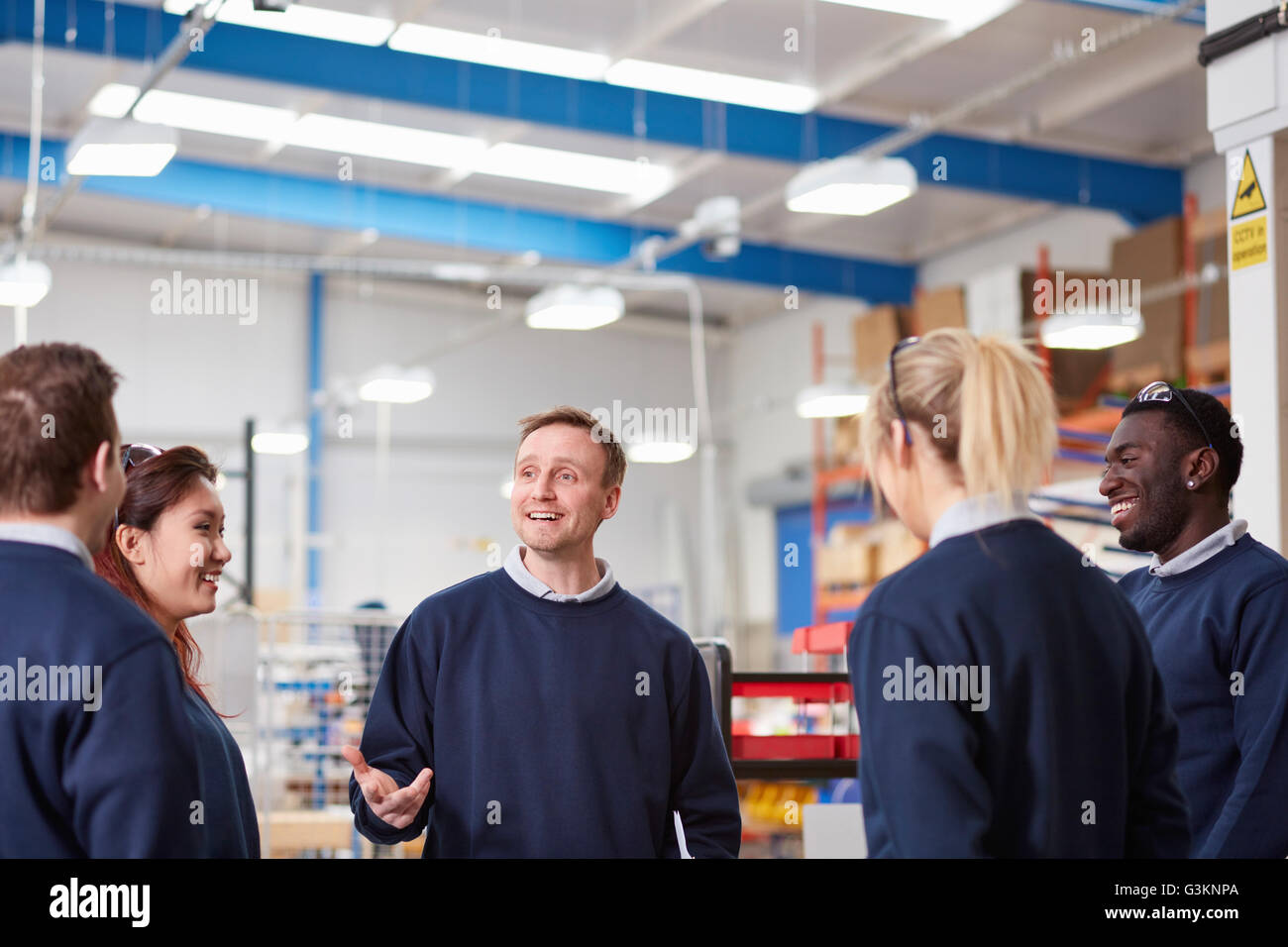 Manager explaining to team in manufacturing factory - Stock Image