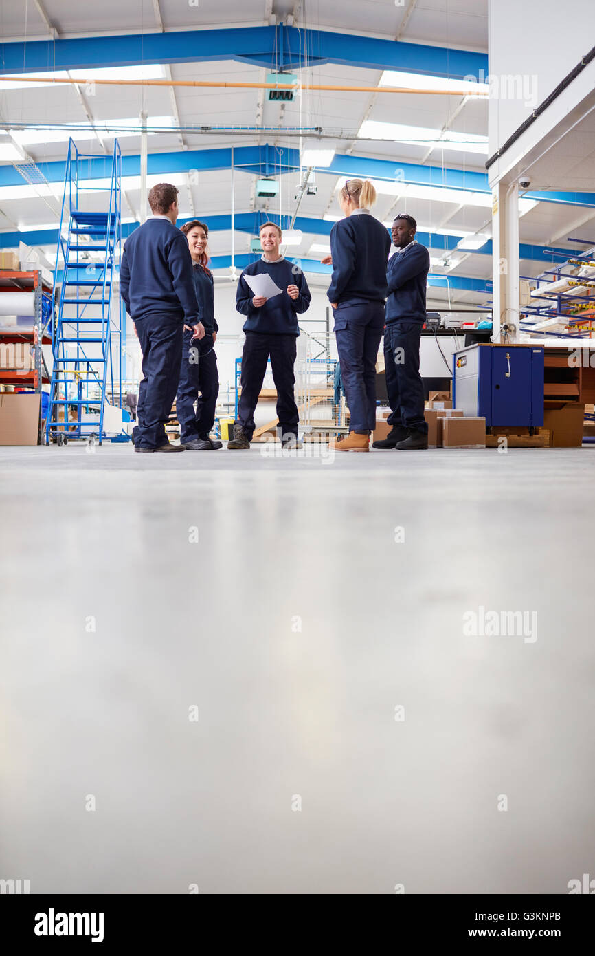 Surface level view of manager explaining to team in manufacturing factory - Stock Image