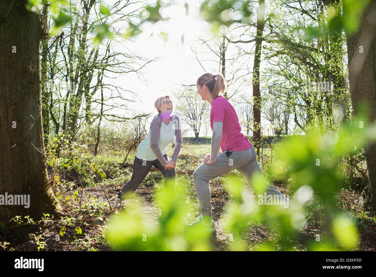 Women face to face in forest hands on knee lunging Stock Photo
