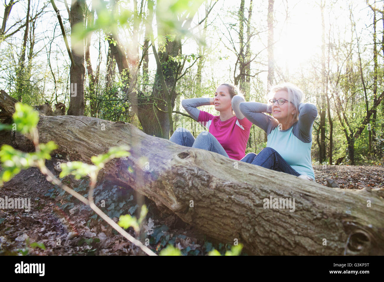 Women in forest hands behind head doing sit up against fallen tree - Stock Image