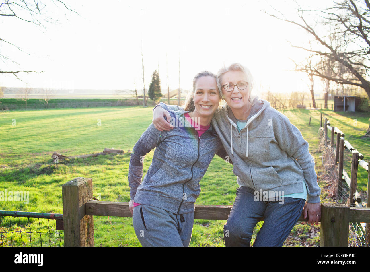Women wearing sports clothing leaning against fence looking at camera hugging and smiling Stock Photo