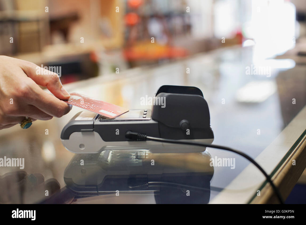 Cropped view of womens hand using credit card to make contactless payment on chip and pin machine Stock Photo