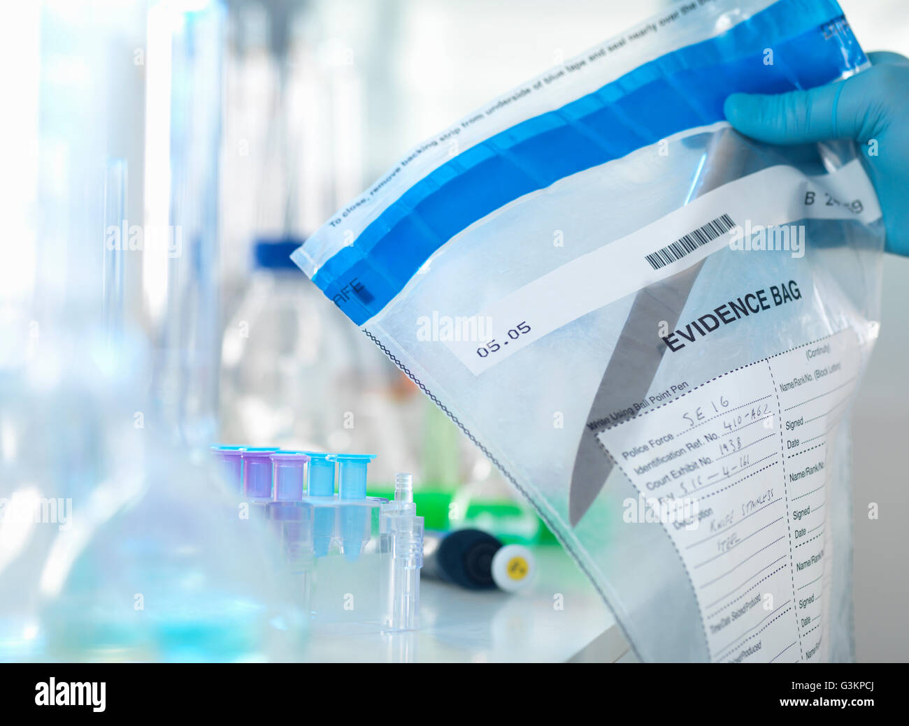 Forensic scientist preparing a knife taken from a scene of crime for DNA analysis - Stock Image