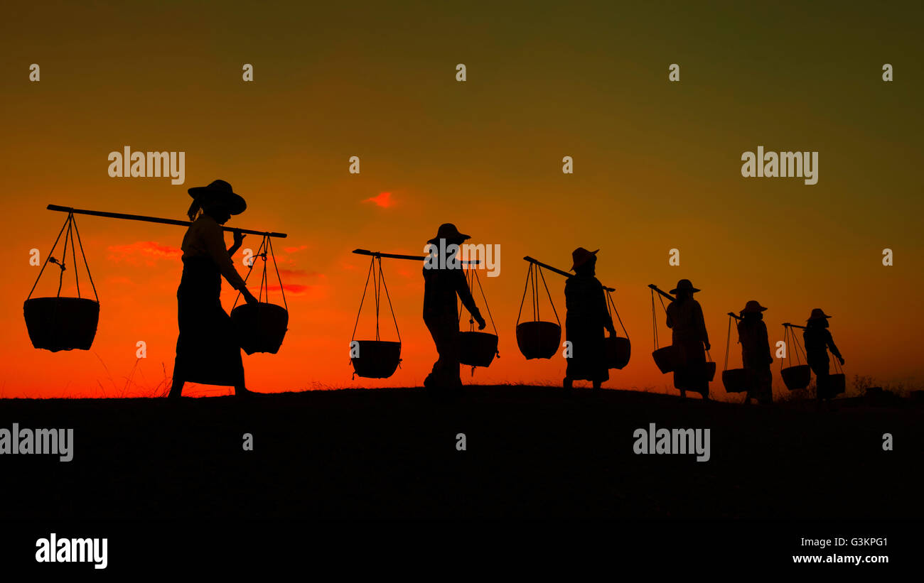 Silhouette of workers carrying yoke and buckets at sunset, Myanmar - Stock Image