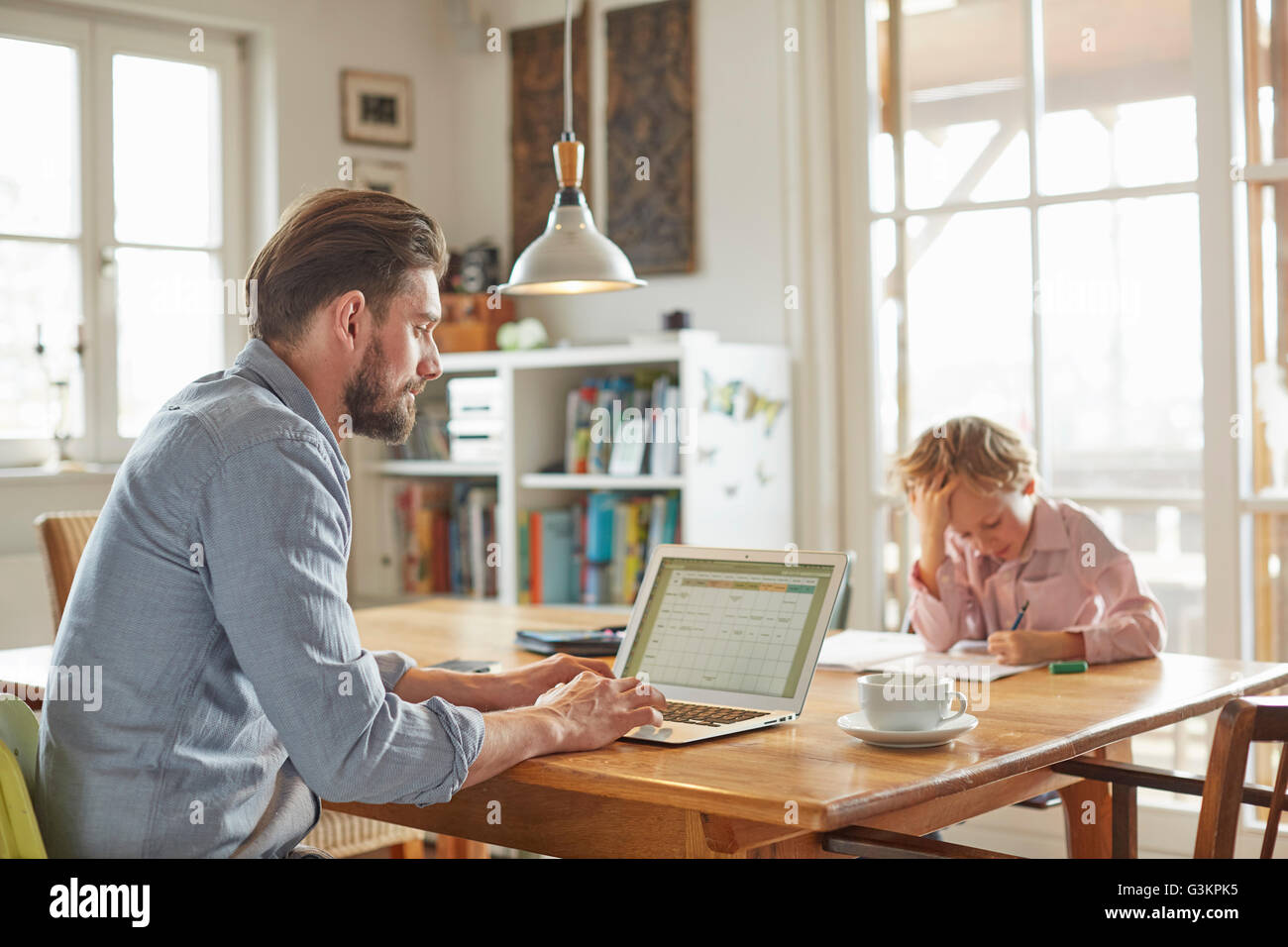 Father and son working in home office - Stock Image