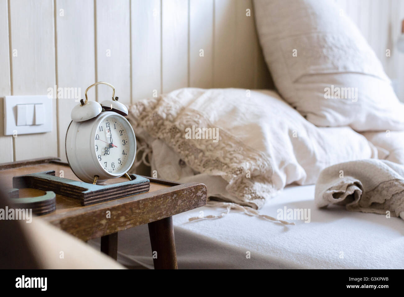 unmade bed alarm clock on bedside table stock image - Bedroom Clock