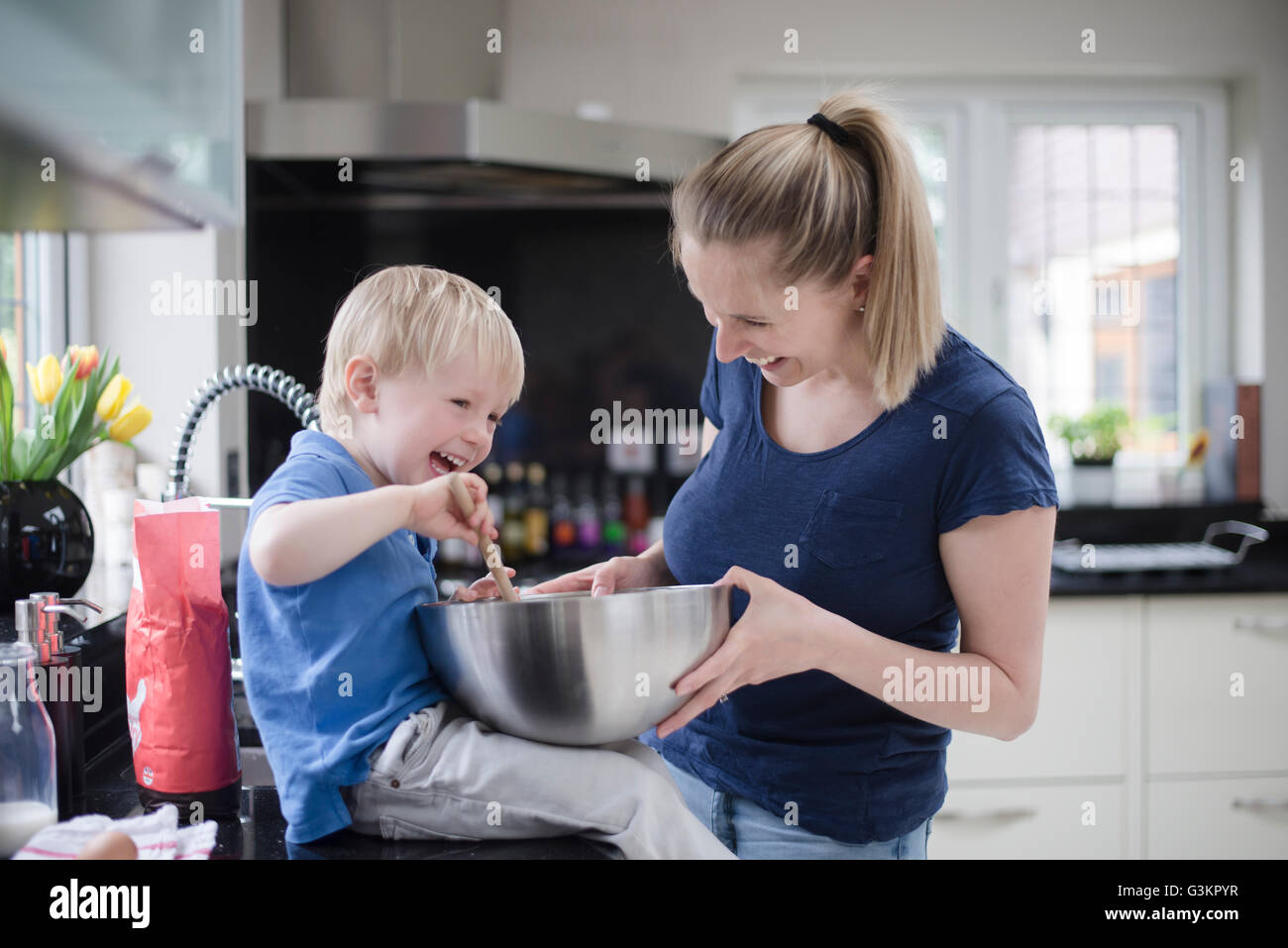 Mother and son fooling around whilst baking, stirring mixture in mixing bowl Stock Photo