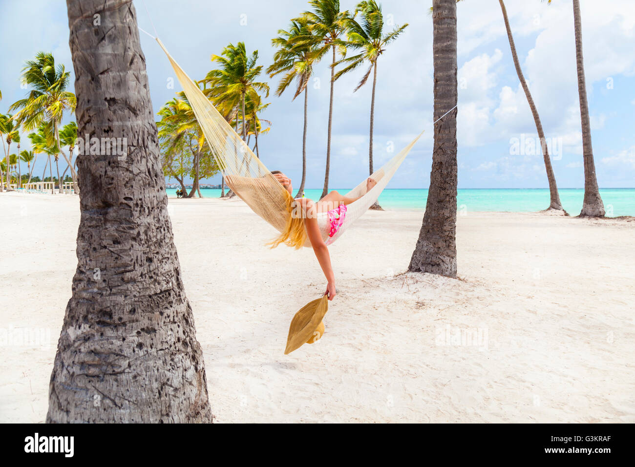Young woman sunbathing in palm tree hammock at beach, Dominican Republic, The Caribbean - Stock Image