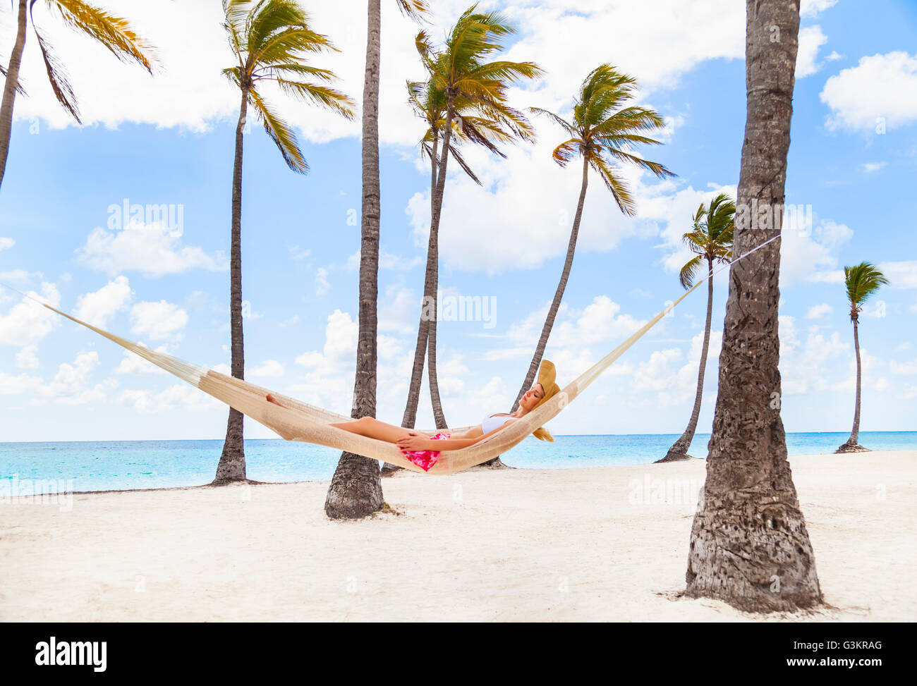 Young woman reclining in palm tree hammock at beach, Dominican Republic, The Caribbean - Stock Image