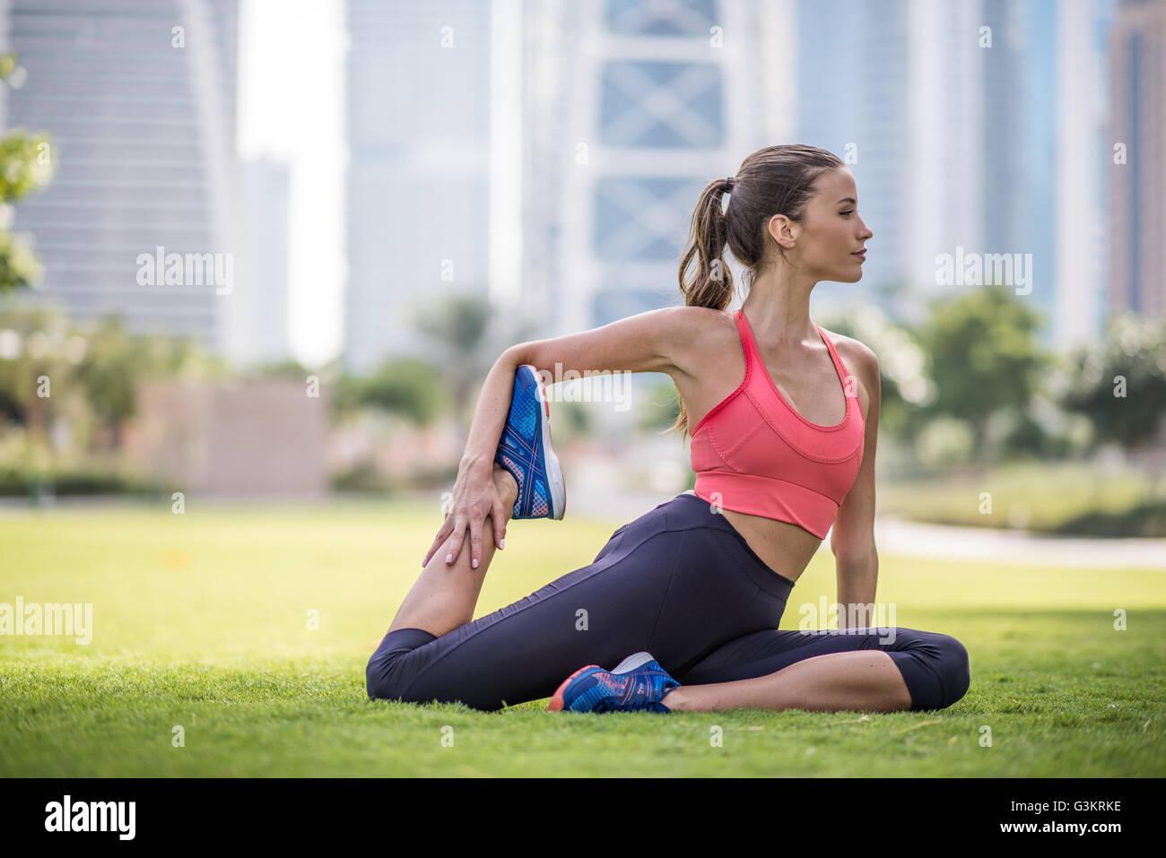 Woman practicing yoga pose in park, Dubai, United Arab Emirates - Stock Image