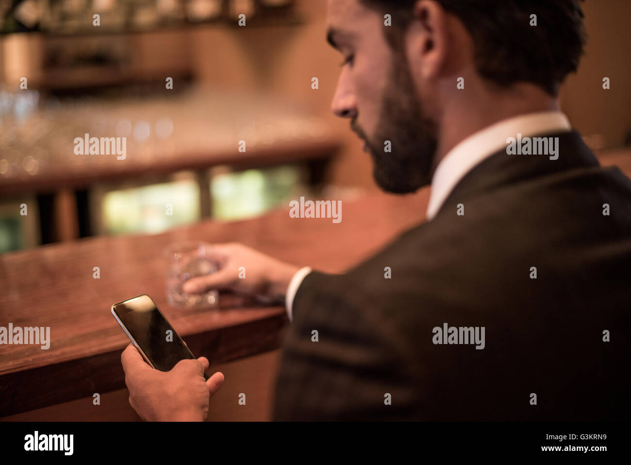 Businessman reading smartphone text at hotel bar - Stock Image