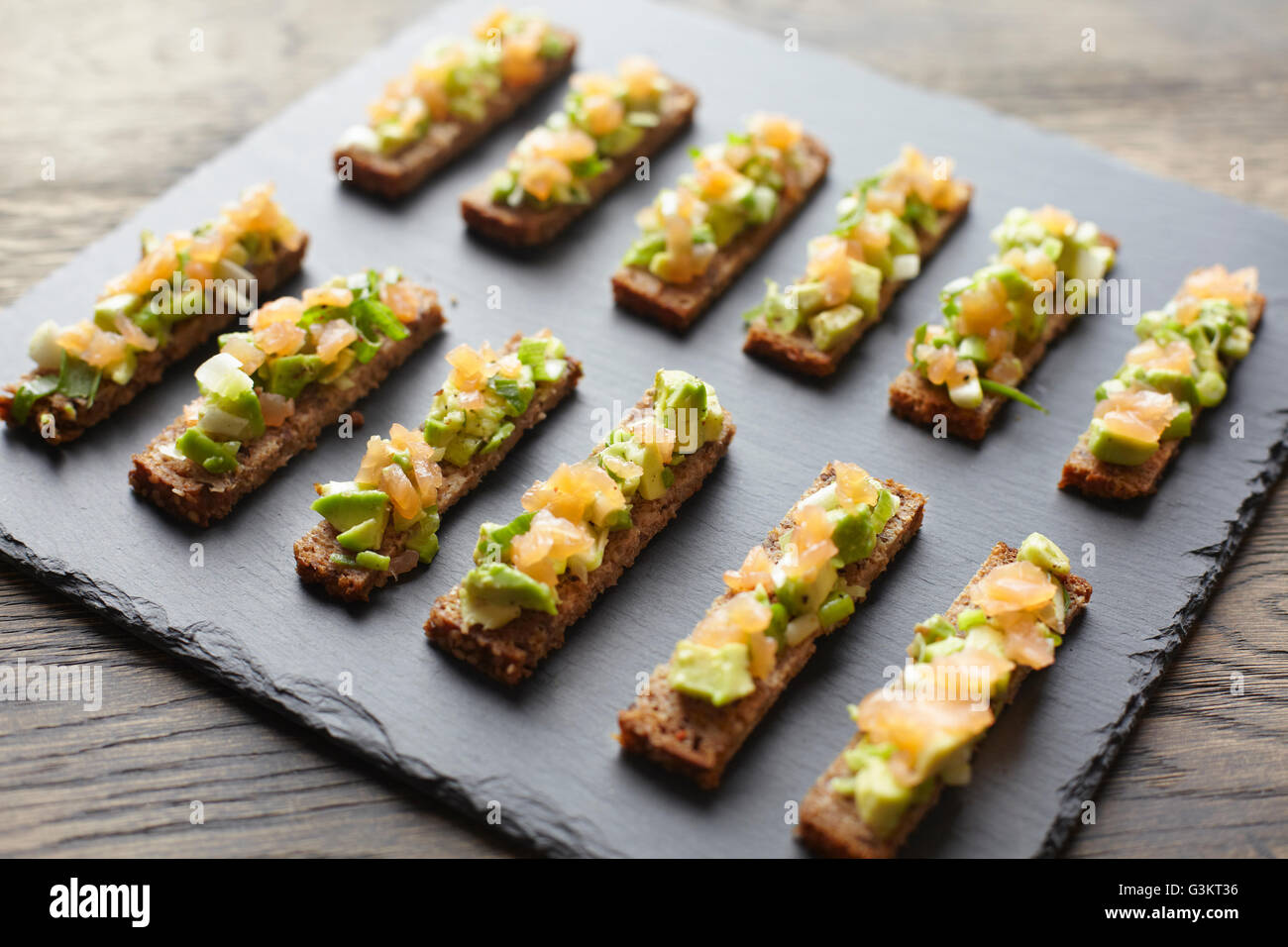 Guacamole, smoked salmon and rye bread canapes - Stock Image