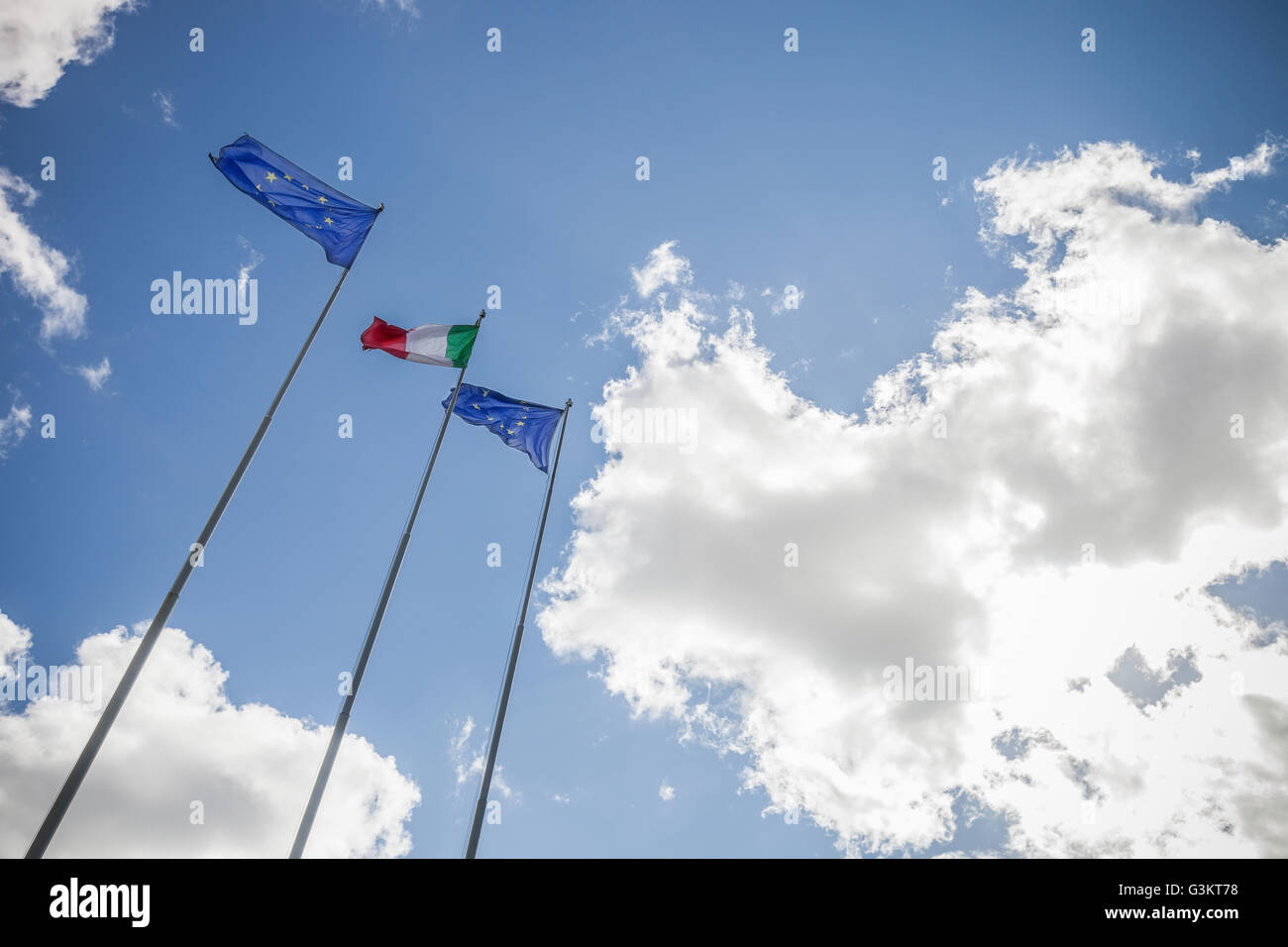 Low angle view of flags flapping in wind on flagpole, Italy - Stock Image