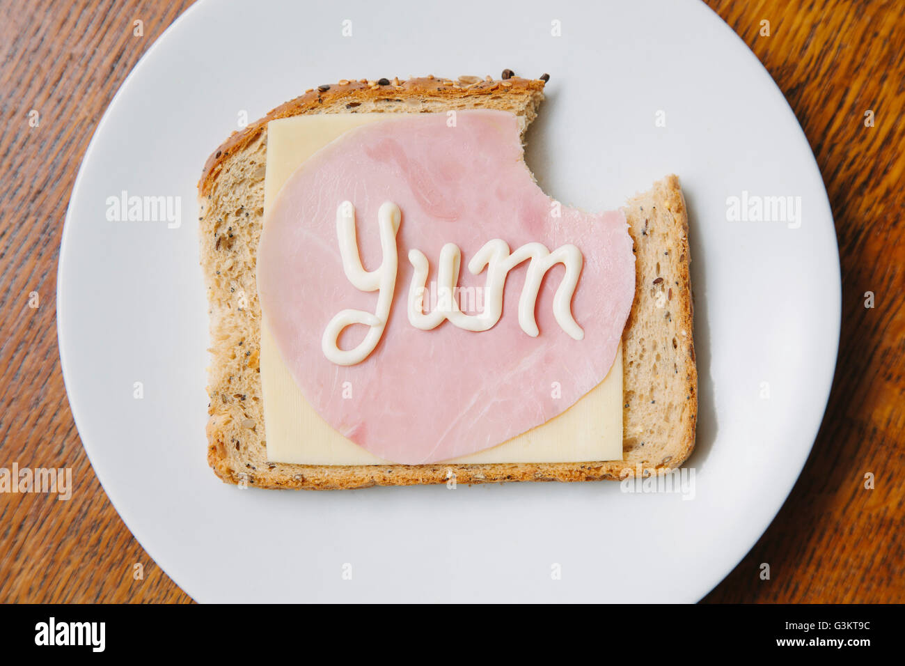 Overhead view of the word yum written on ham and cheese   on bread in mayonnaise - Stock Image