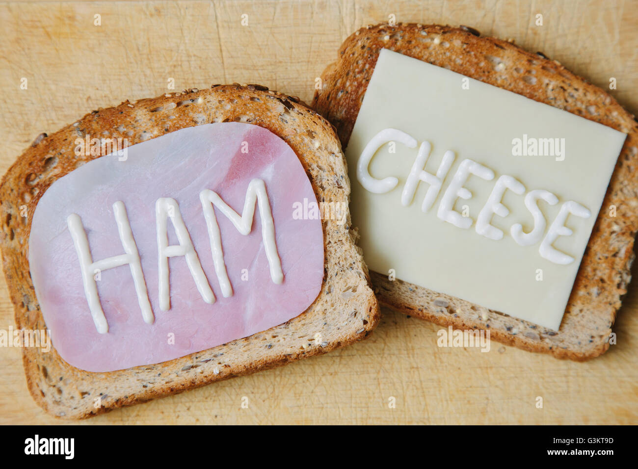 Overhead view of the words ham and cheese written on toast in mayonnaise - Stock Image