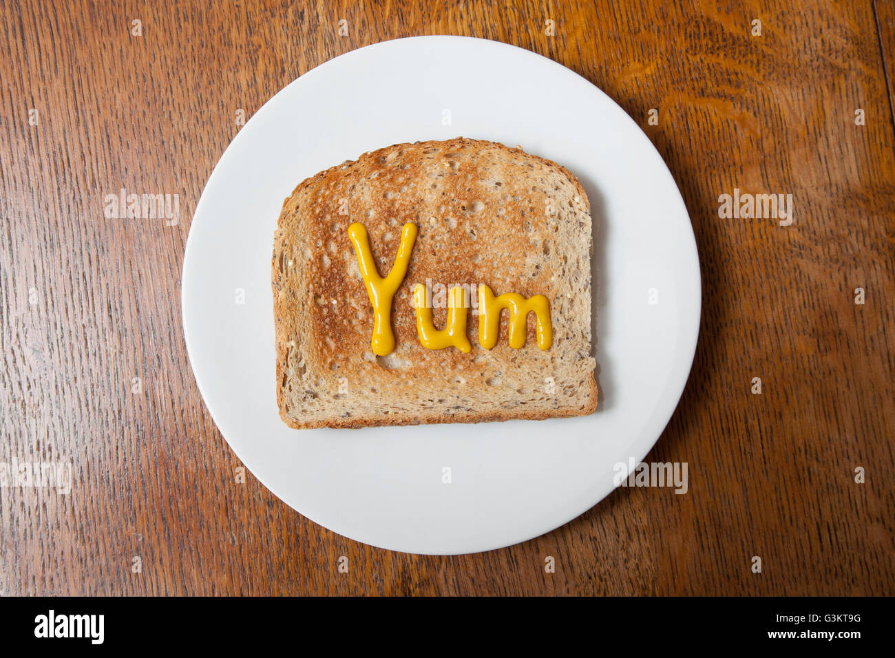 Overhead view of the word yum written on ham on toast in mustard - Stock Image