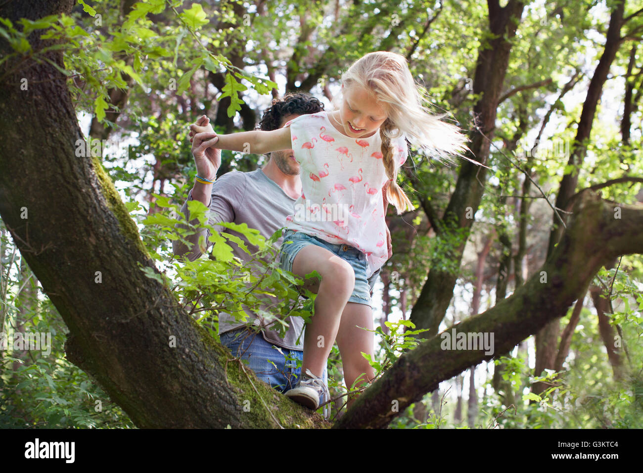 Father helping daughter to climb tree - Stock Image