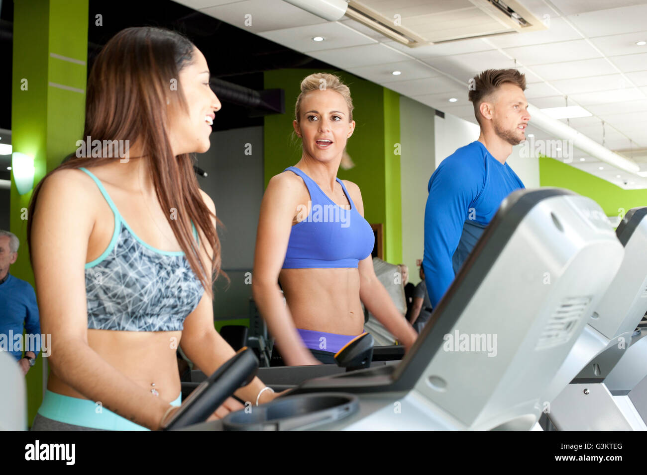 People at gym using exercise machines chatting - Stock Image