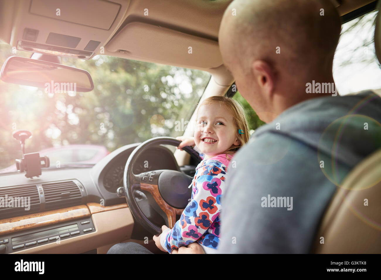 Over shoulder view of daughter sitting on father lap driving car - Stock Image