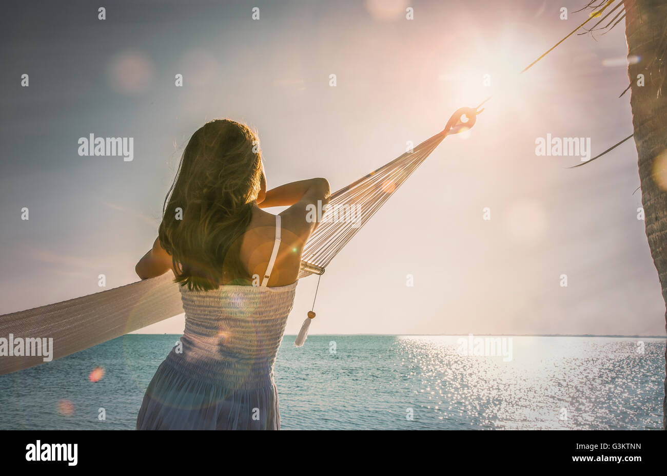 Young woman leaning against hammock watching sunset on Miami Beach, Florida, USA - Stock Image