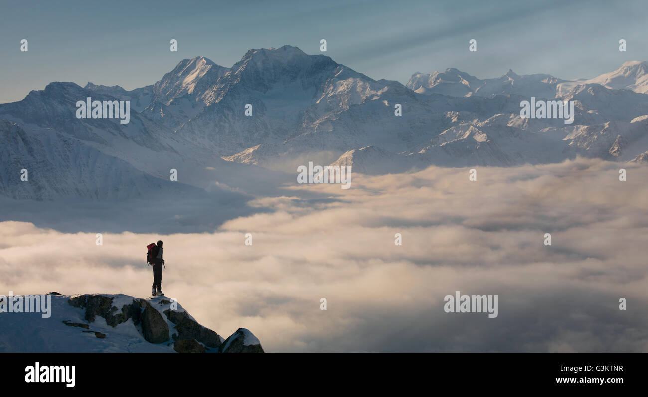 Climber on a peak emerging from fog in the Alps, Bettmeralp, Valais, Switzerland - Stock Image