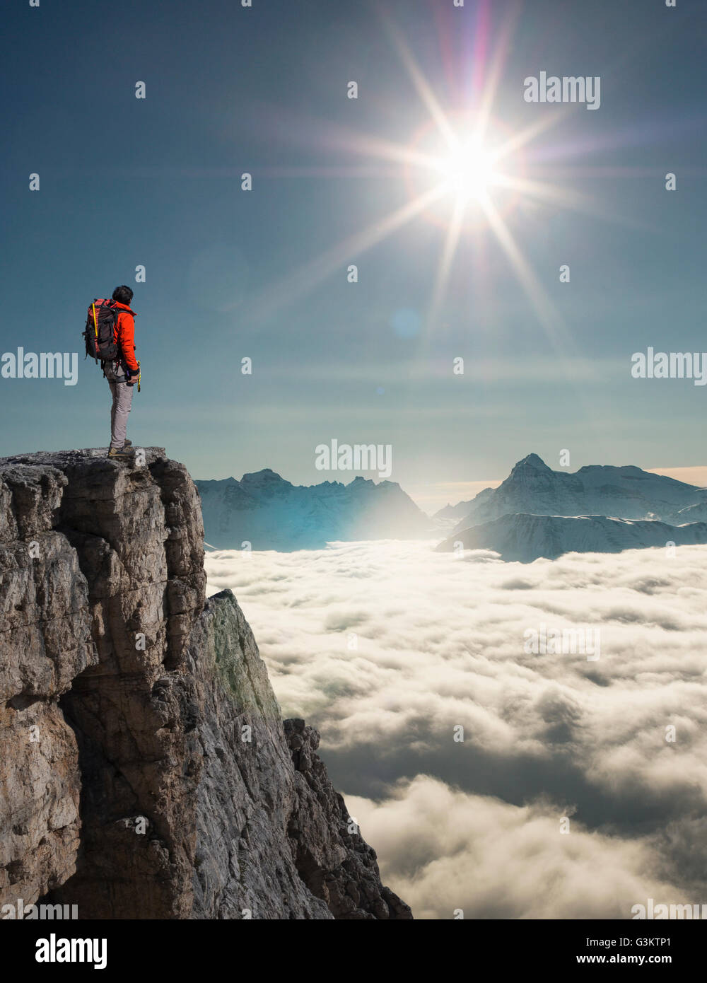 Climber looking out from peak emerging from fog in the Alps, Bettmeralp, Valais, Switzerland - Stock Image