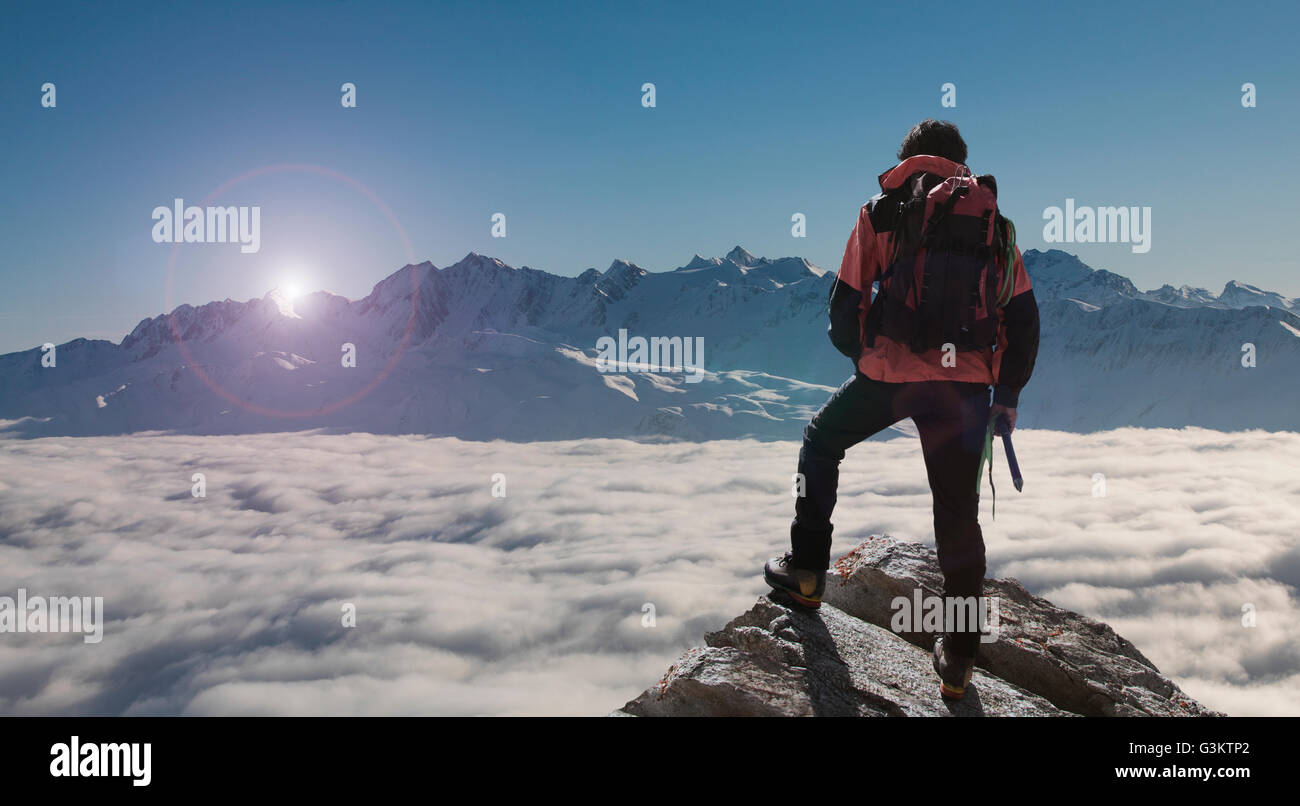 Climber looking out at sunset from peak emerging from fog, Bettmeralp, Valais, Switzerland - Stock Image