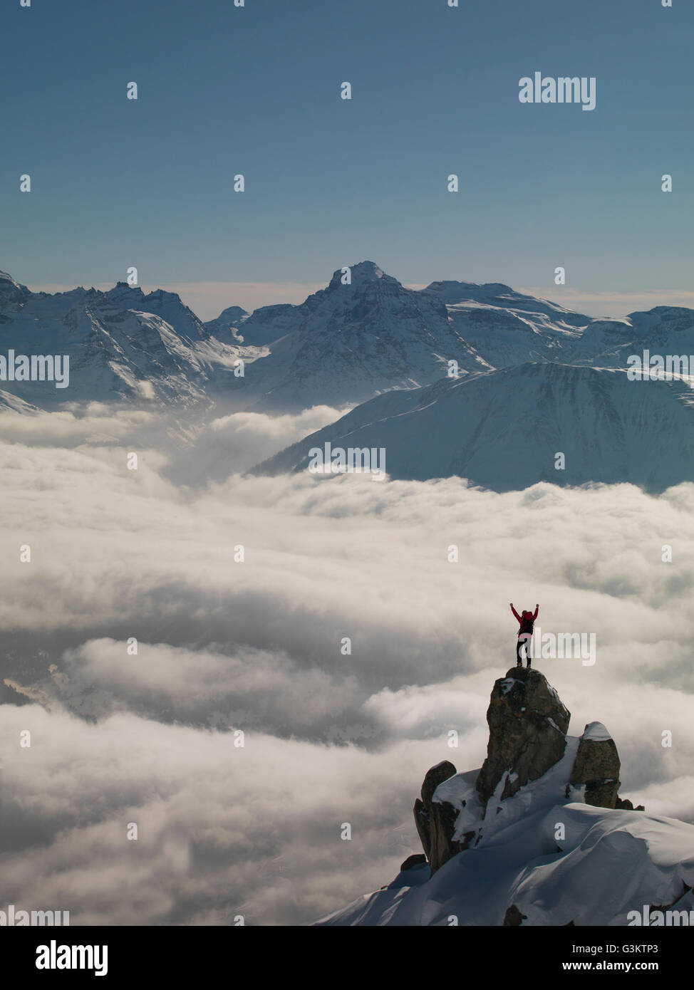 Climber celebrating on peak emerging from fog, Bettmeralp, Valais, Switzerland - Stock Image