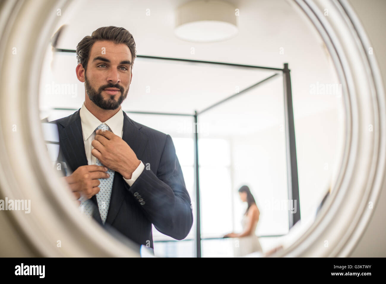 Mirror reflection of young businessman adjusting shirt and tie in hotel room, Dubai, United Arab Emirates - Stock Image