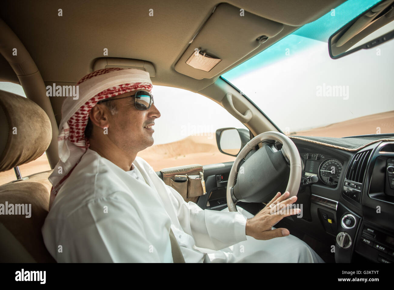 Middle eastern man wearing traditional clothes driving off road vehicle in desert, Dubai, United Arab Emirates - Stock Image