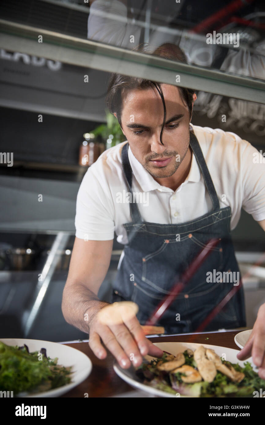 Restaurateur preparing salad behind service counter - Stock Image