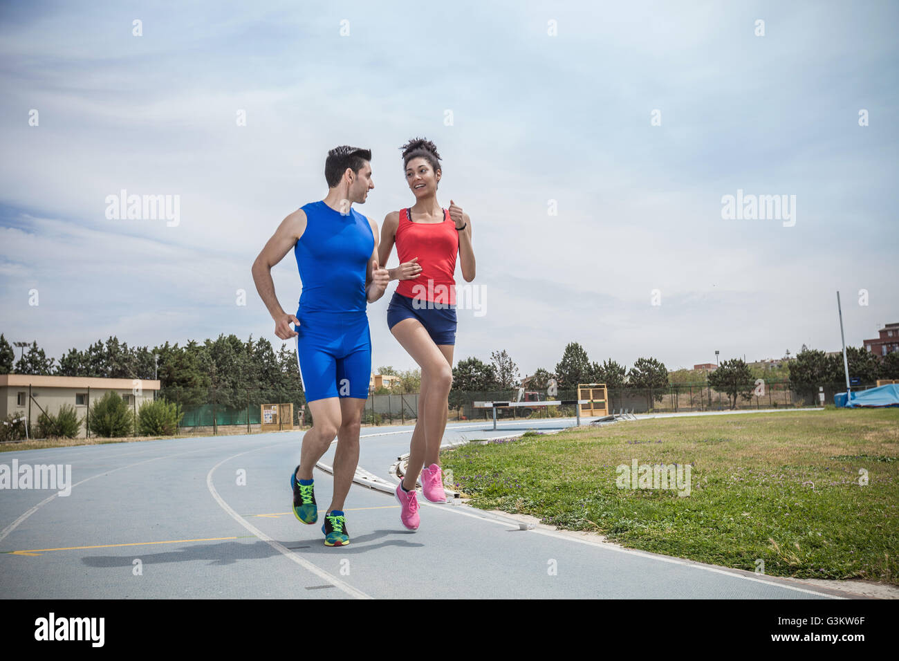 Young male and female runners training on running track - Stock Image