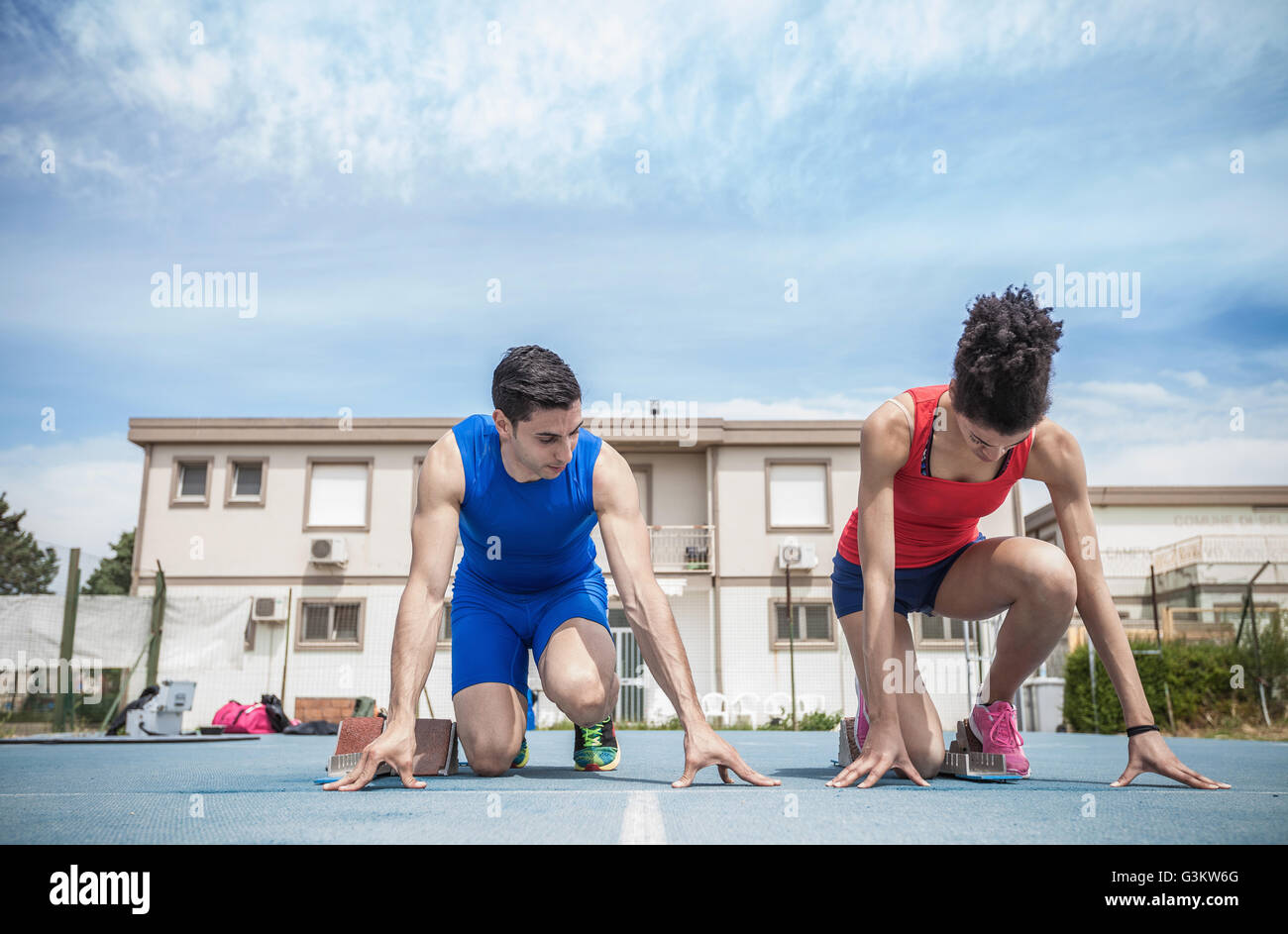 Young male and female sprinters training on running track - Stock Image