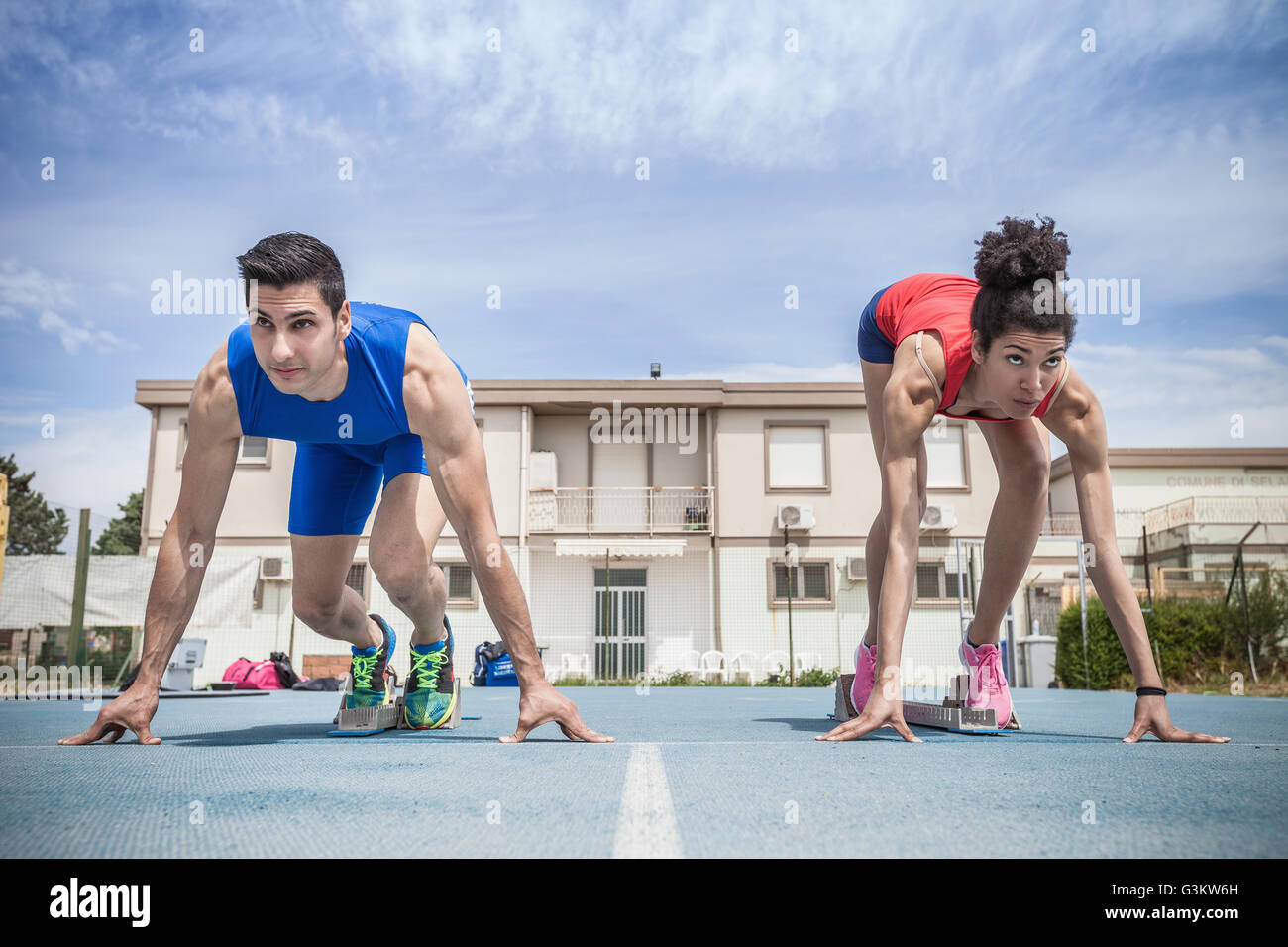Young male and female sprinters on their marks on running track - Stock Image