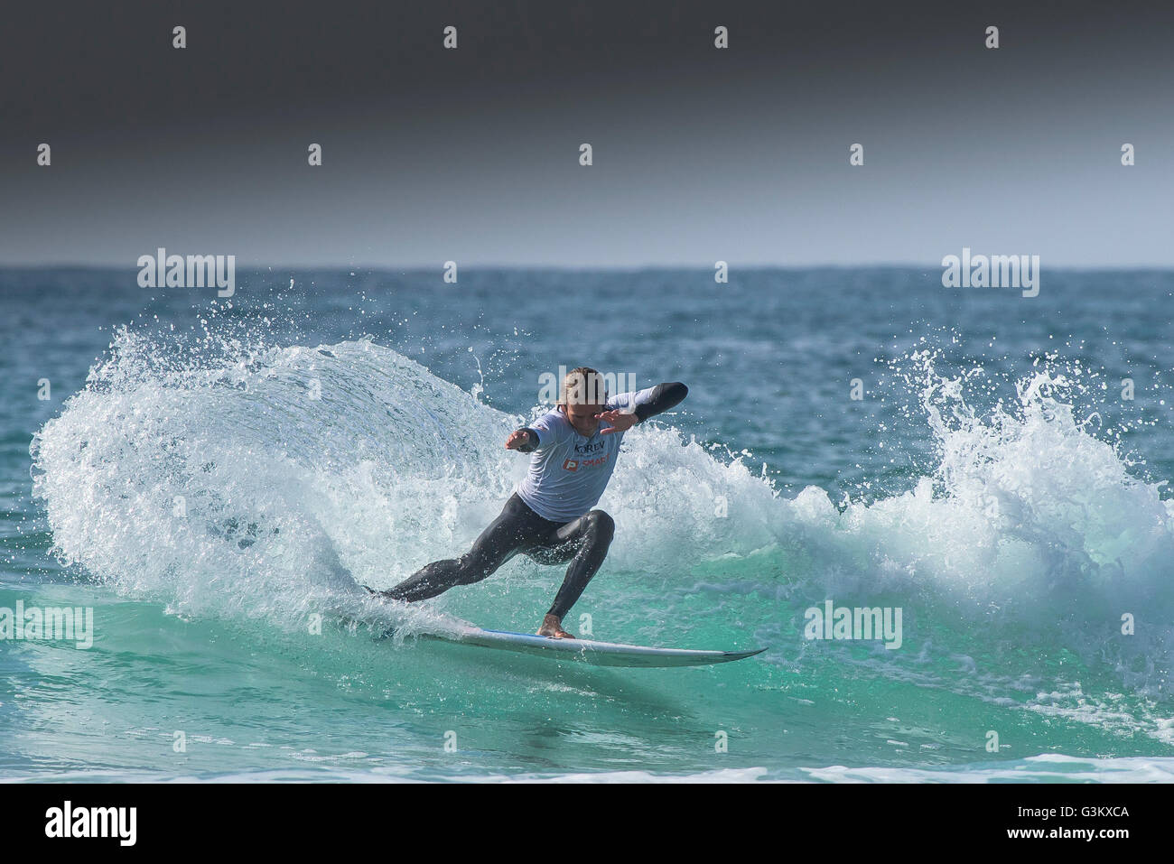 A surfer in spectacular action as he competes in a UK Pro Surf Tour competition at Fistral in Newquay, Cornwall. - Stock Image