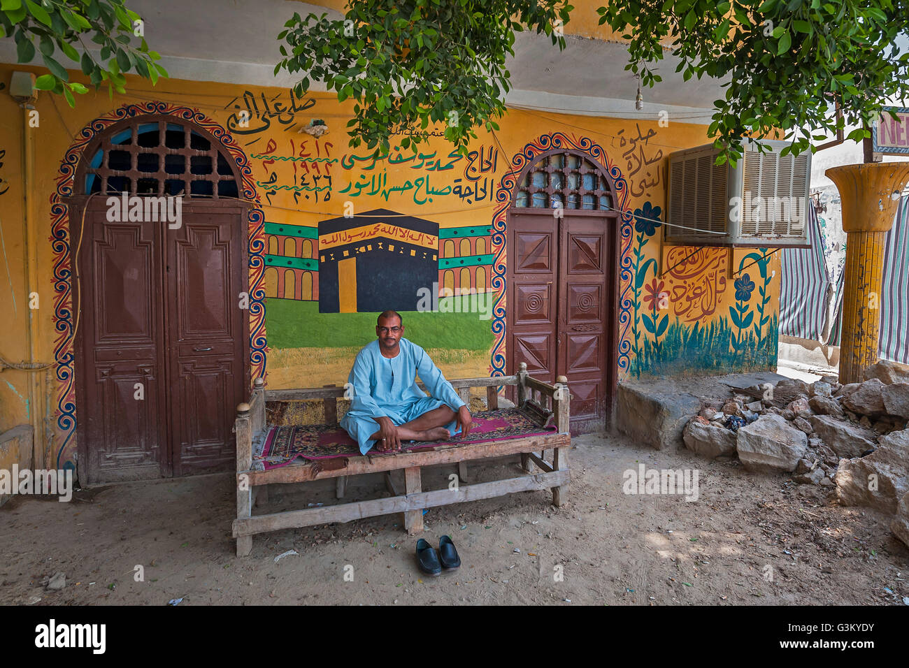 Man, Egyptian, sitting in front of his painted house, Valley of the Kings, Luxor, Egypt - Stock Image