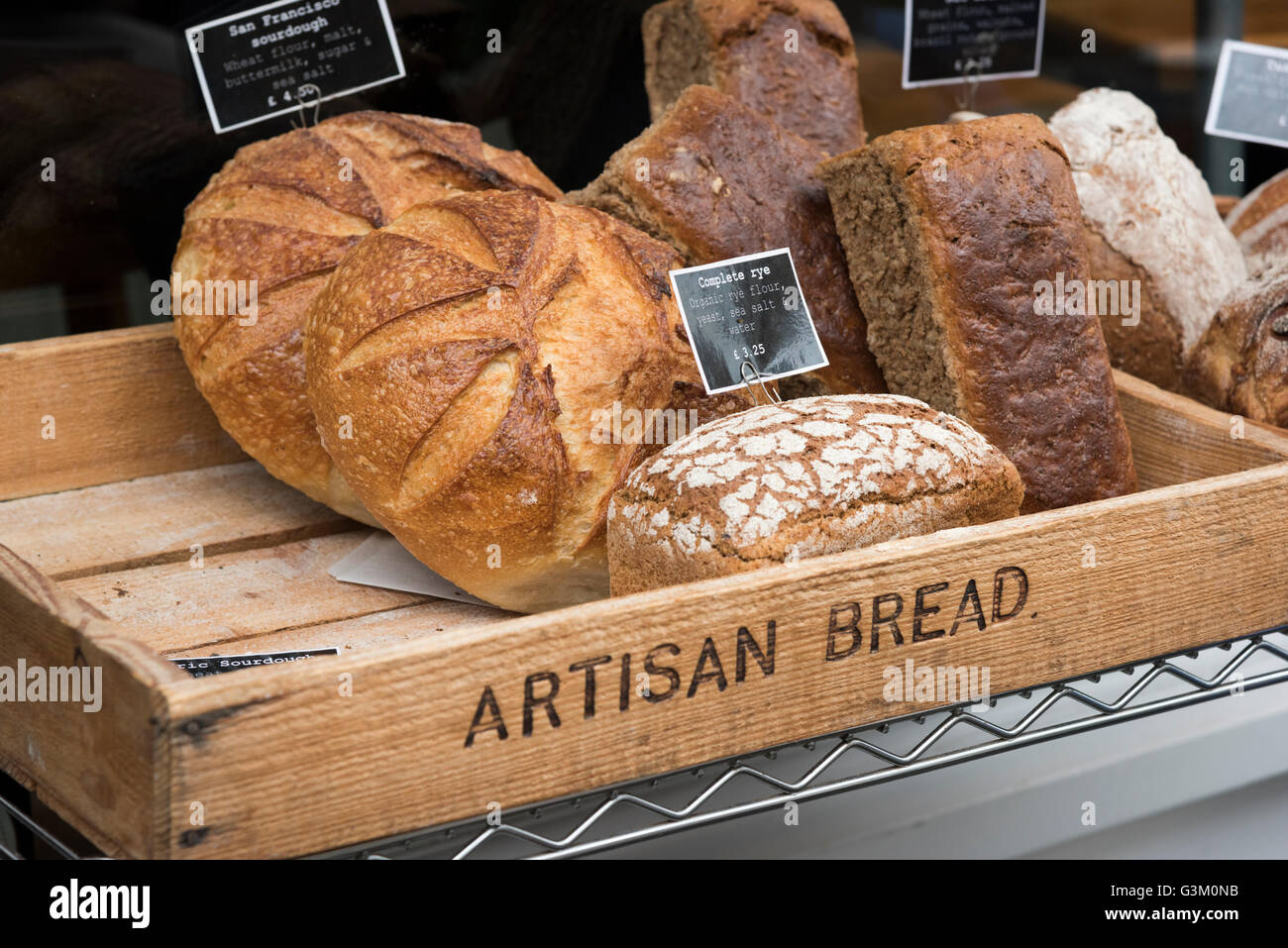 A wooden tray full of artisan bread for sale in the UK - Stock Image